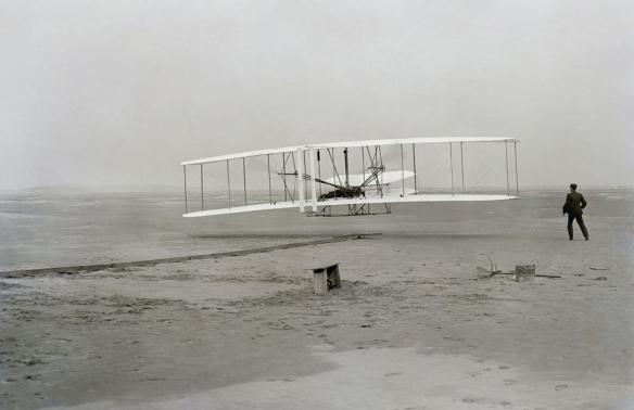 First flight of the Wright Flyer I, December 17, 1903, Orville piloting, Wilbur running at wingtip.